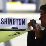 Jackson Droege snaps a photo of one of the shells belonging to the University of Washington crew team before the start of the 2015 Windermere Cup Saturday. Droege and the rest of the his teammates with Mount Baker Rowing Club were among the competitors. -Source: John Lok/The Seattle Times