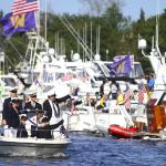 Members of an ambassador crew greet the crowd gathered on one of the log booms before the start of the 2015 Windermere Cup Saturday. -Source: John Lok/The Seattle Times